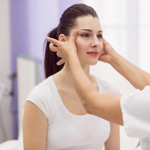 Dermatologist examining female patient skin in clinic