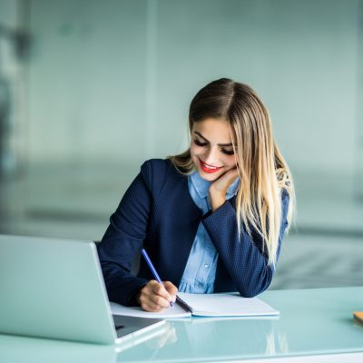 Young pretty woman working with laptop and taking notes on a desktop at Office