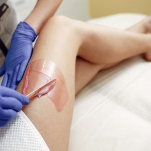Beautiful girl doing hair removal. Woman in beauty salon
